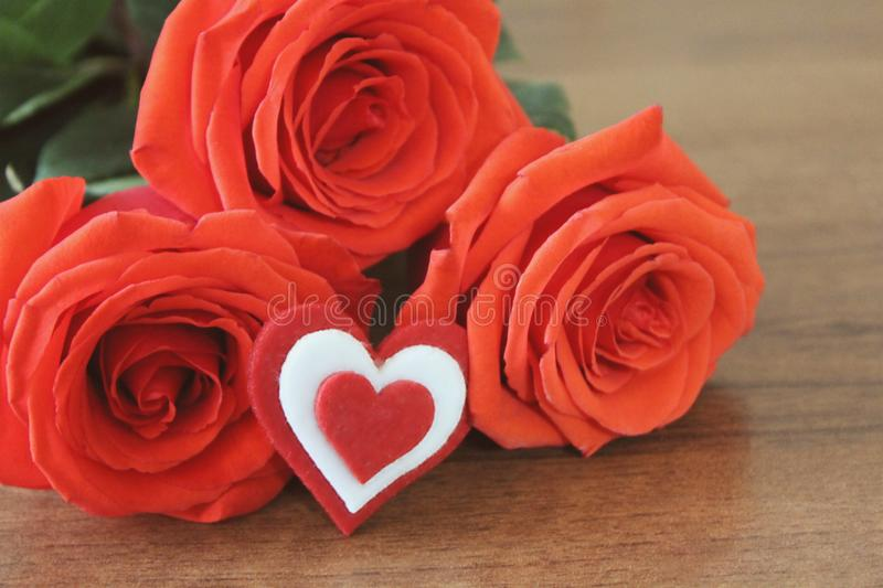 Red roses in a bouguet with a souvenir in the shape of a heart red and white color s lie on a wooden table brown. Macro. stock images