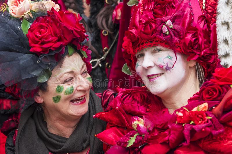 Beautiful costumed senior women with handmade dress full of roses at carnival in Zurich royalty free stock photo