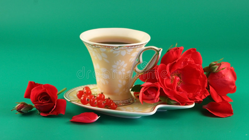 Red roses and a cup of tea royalty free stock photo
