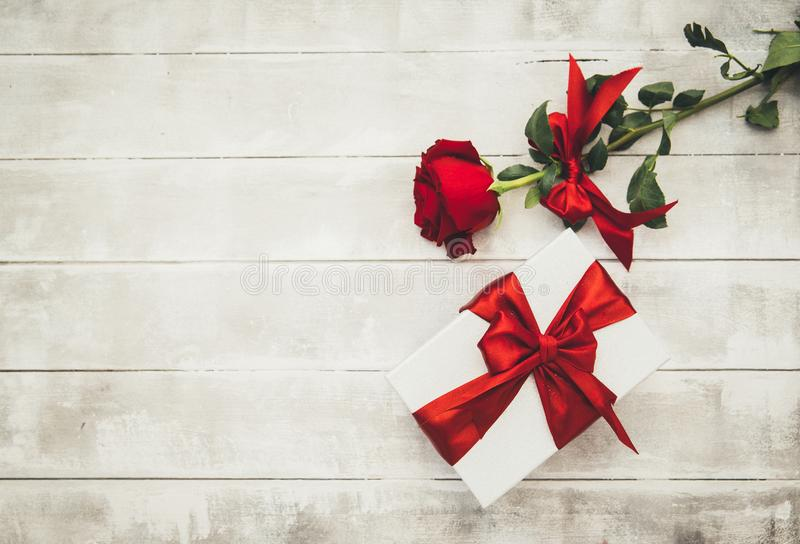 Red roses and gift box on a wooden table. Happy Valentines Day stock images
