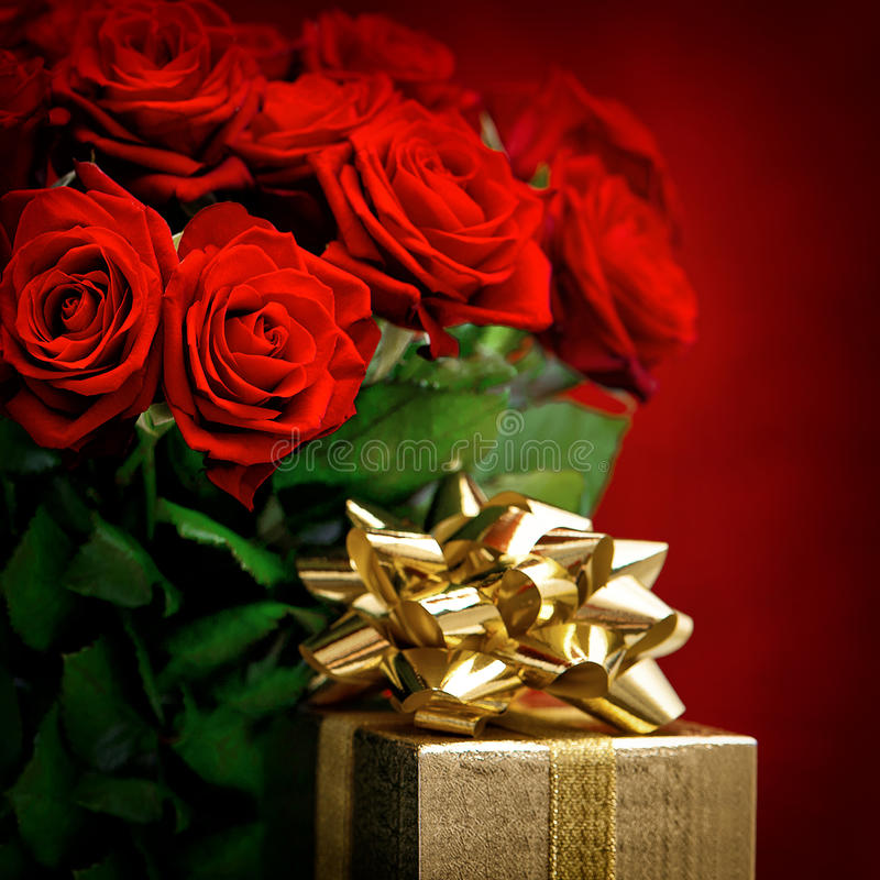 Red roses and golden gift box. Festive decoration stock images