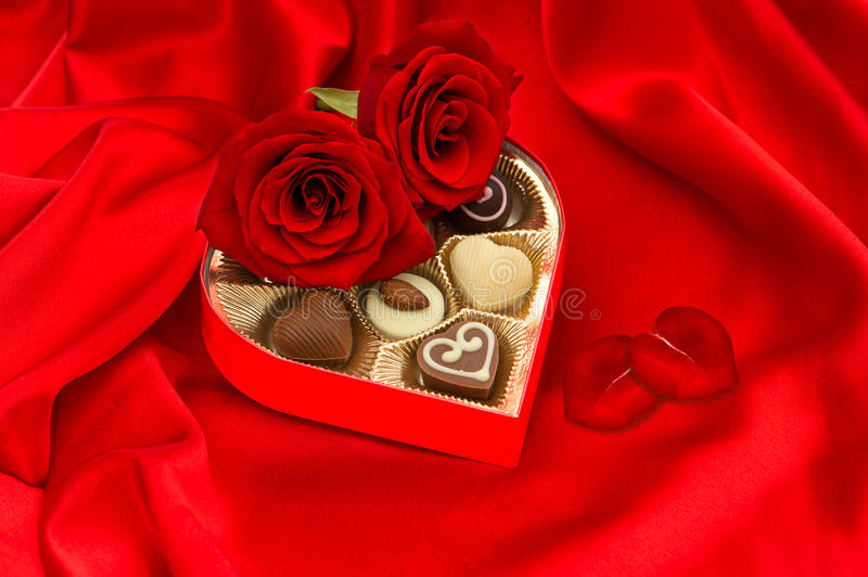 Red roses with heart petals and chocolate pralines. Red roses and delicious chocolate pralines in golden heart shape gift box on silk background stock photo
