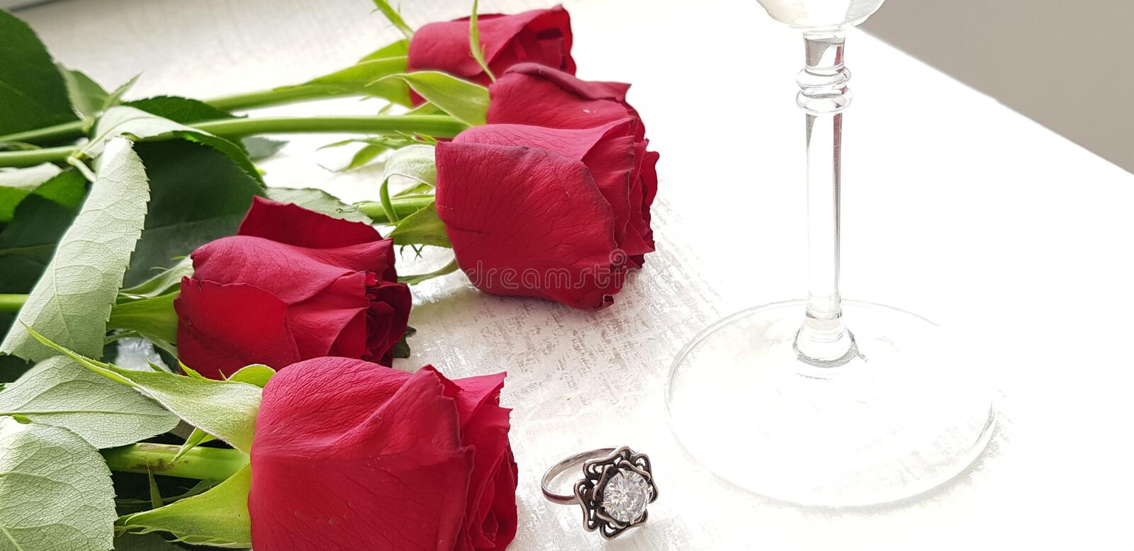 Red roses lay on white table near silver ring with big clear diamond stock images
