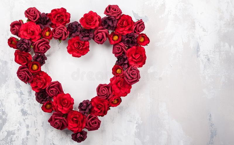 Red roses in shape of heart. On the light gray vintage background royalty free stock image