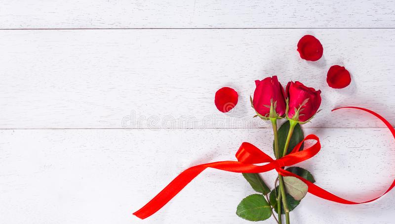 Red roses tied with ribbon. Red roses tied with red ribbon on white wooden table stock photography