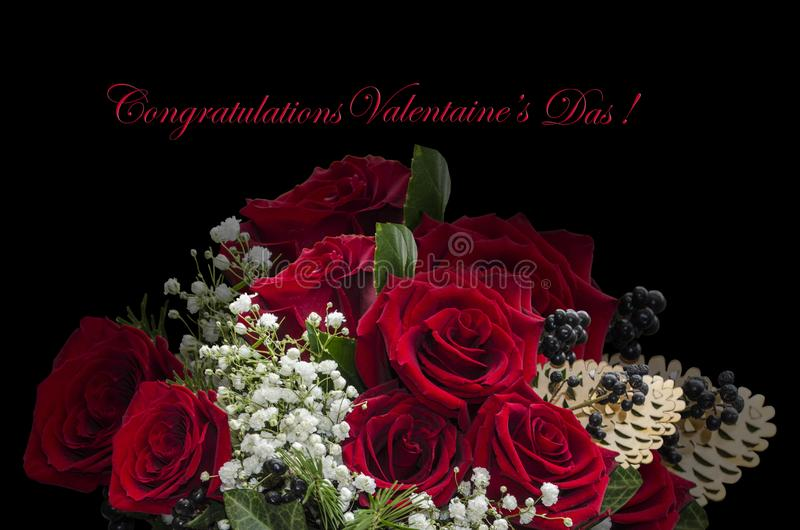 Red roses, twigs with white small flowers and black berries and congratulations on a black background royalty free stock photography