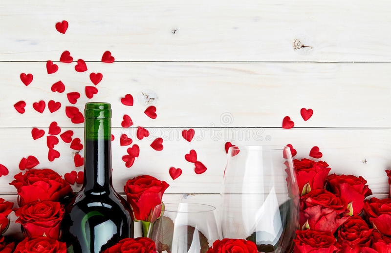 Red roses and wine on white background stock photo