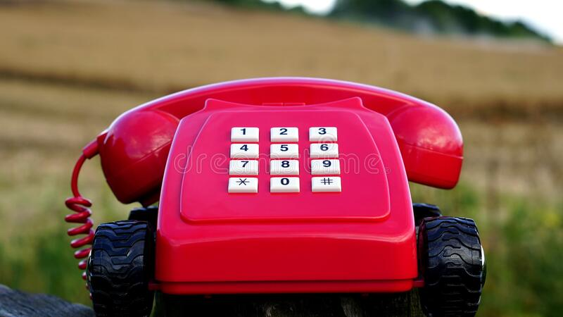 Red Rotary Phone With Black Wheels Near Brown Grasses during Day Time stock image