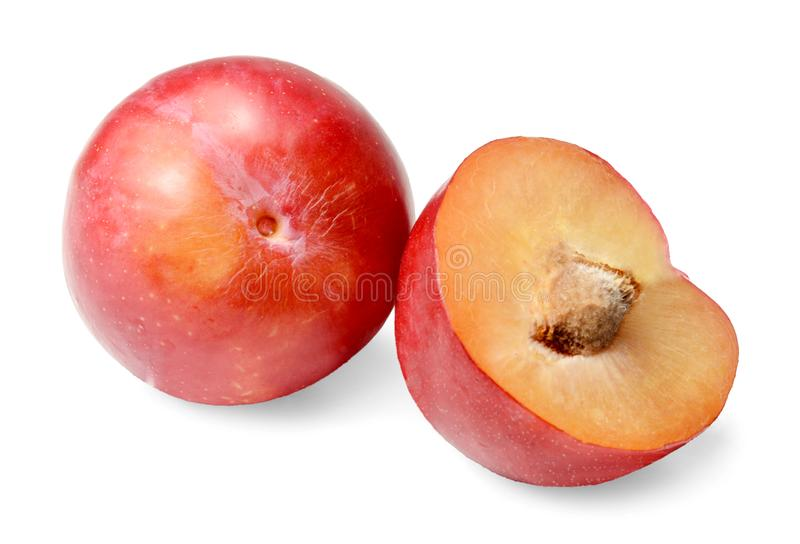 Red round plum. Whole and half. Isolated on white Close-up. royalty free stock image