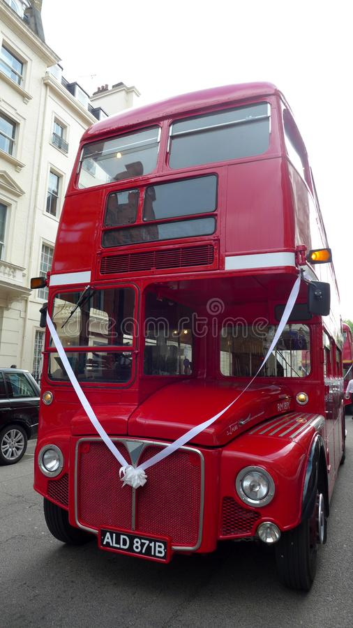 A red Routemaster bus on a London street with ribbon wedding celebration. London, Front view royalty free stock photo