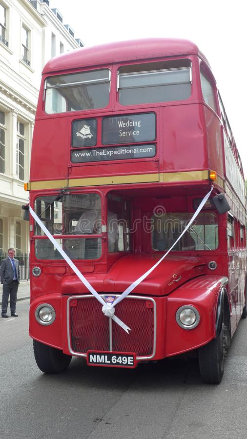 A red Routemaster bus on a London street with ribbon wedding celebration. London, Front view stock photos