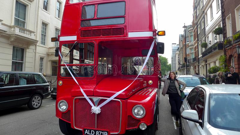 A red Routemaster bus on a London street with ribbon wedding celebration. A woman leaning on the red Routemaster bus on a London street with ribbon wedding royalty free stock photos