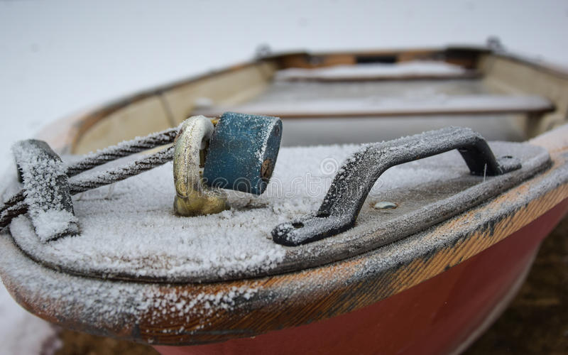 red rowing boat with blue padlock filled with frozen water royalty free stock images
