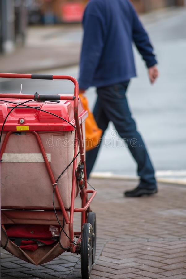 Red royal mail trolley chained to gate with man walking past in the morning. Bright red royal mail push trolley barrow chained to cast iron fence with road and royalty free stock images