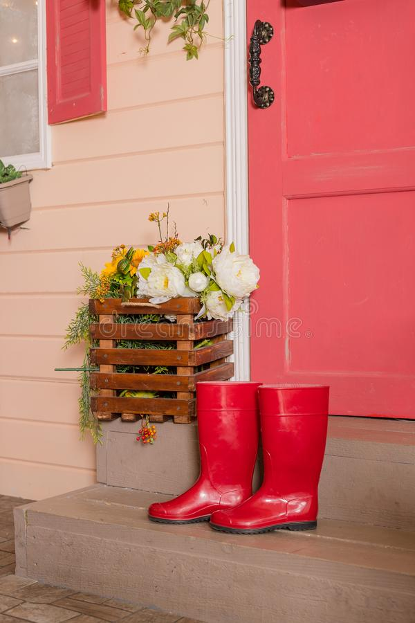 Red rubber shoes on the steps of the house.women water-proof boots.bright red gardening boots.trendy shoe for Rainy day spring, royalty free stock photo