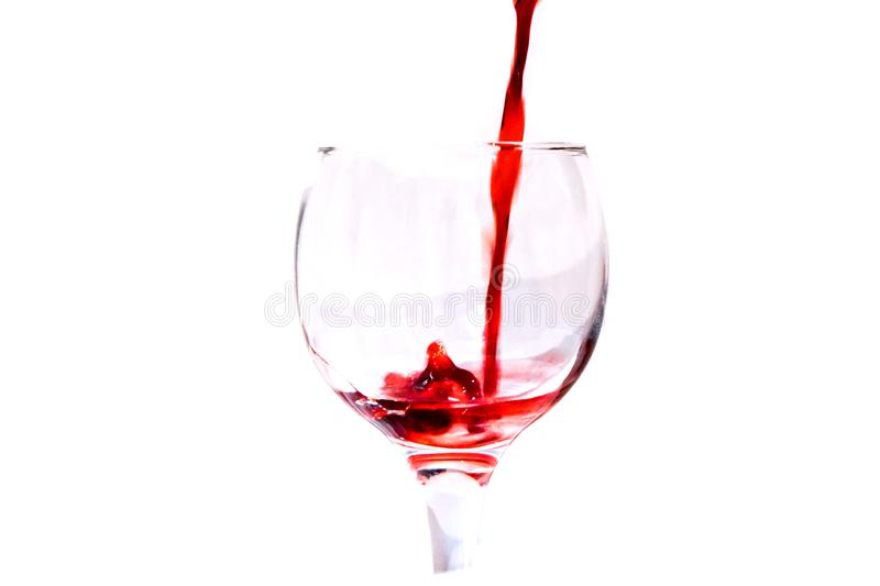 Red ruby wine poured vertically down into a glass isolate. Red ruby wine poured vertically down into a glass wine glass stock image