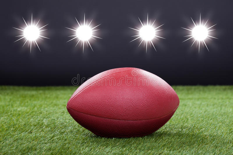 Red rugby ball. Red Leather Rugby Ball On Pitch Field royalty free stock photo