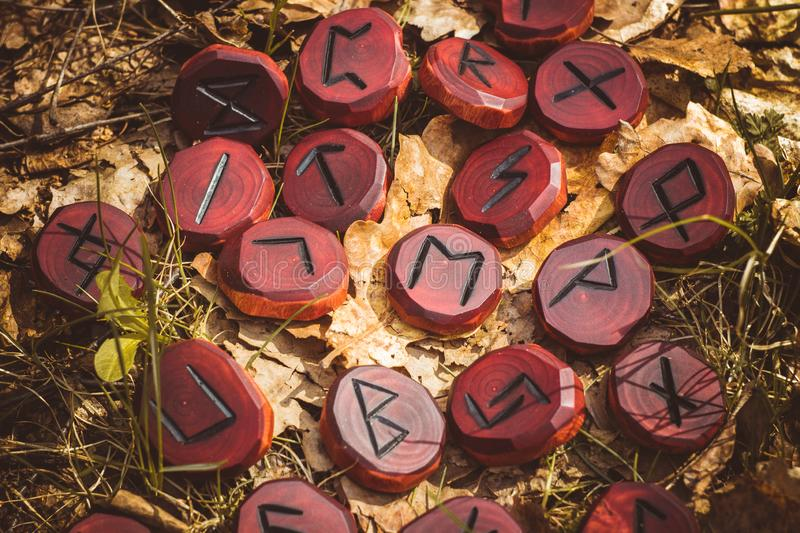 Red runes carved from wood. On the ground royalty free stock photos