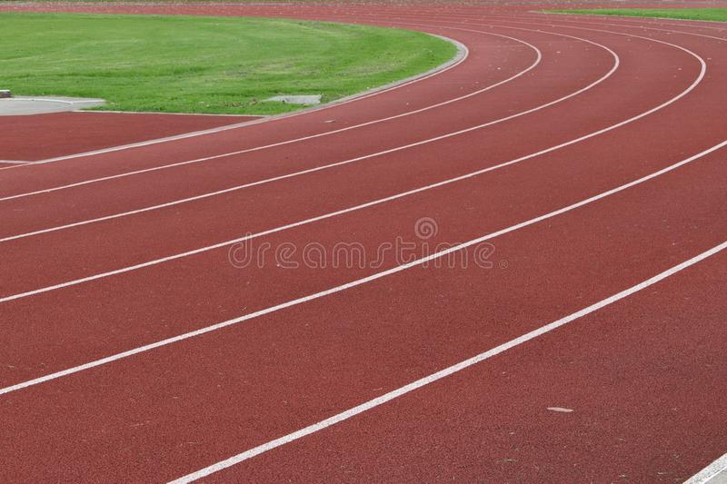 Cross section of red running race track. Curved section of red running race track with white lines marking the lanes ready for track and field events stock photo