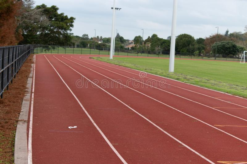 Red running race track long view. Long view of a section of red running race track with lanes clearly marked with white lines for long distance track and field stock photography