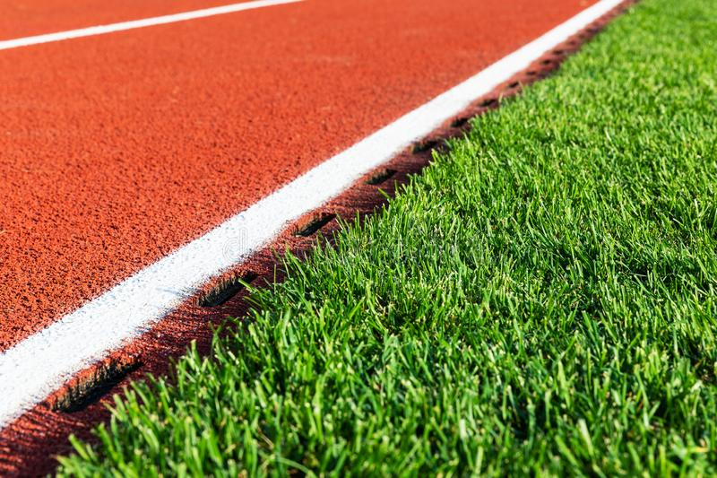 Red running track and green grass field at the sport stadium. Creative abstract competition concept: macro view of the fragment of red running track and green stock image