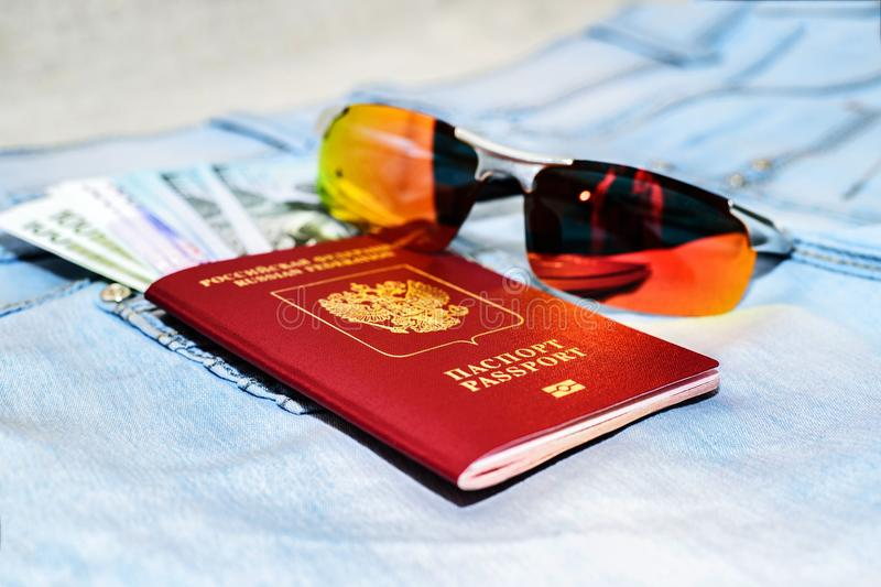 Red russian Passport with money bills and glasses on jeans. The concept of travel. stock images
