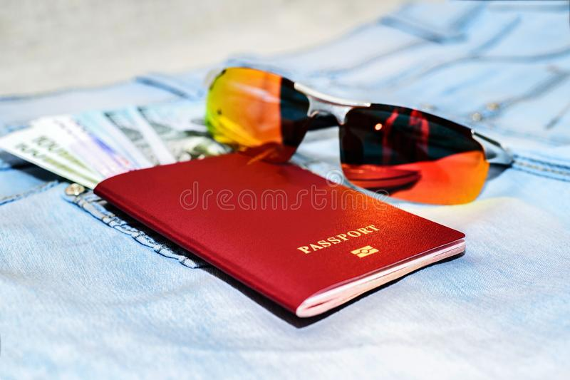 Red russian Passport with money bills and glasses on jeans. The royalty free stock photos
