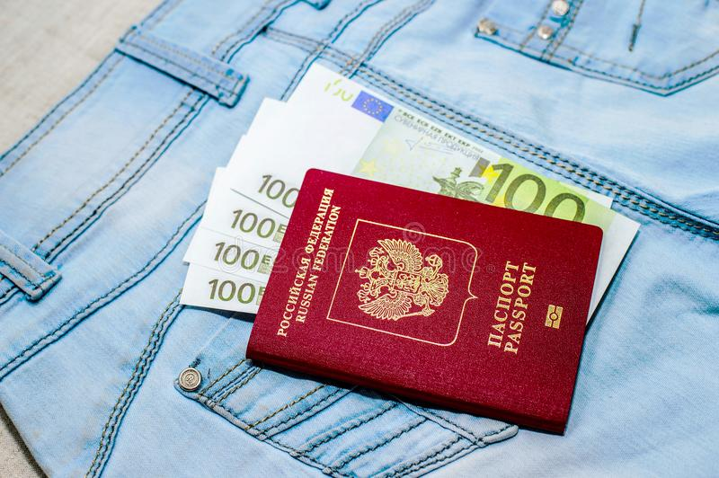 Red russian Passport with money bills on jeans. The concept of travel. royalty free stock photo