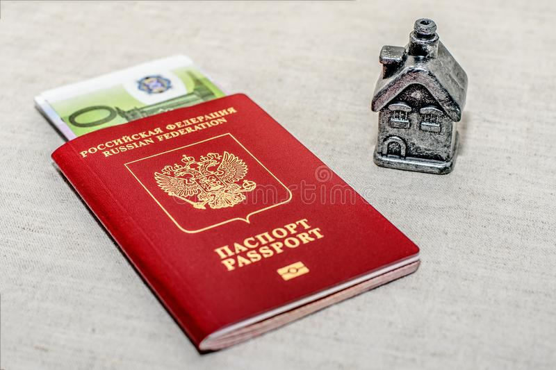 Red russian Passport, money and home - the concept of buying a property. royalty free stock photography