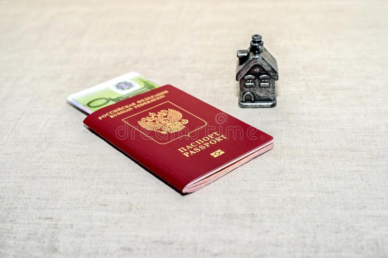 Red russian Passport, money and home - the concept of buying a property. royalty free stock photos