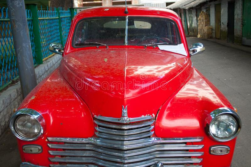 Red russian retro car Pobeda Victory standing in the street stock photography
