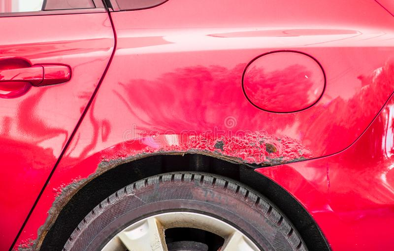Red rusted and scratched car with damaged rusty paint in crash accident or parking lot stock image