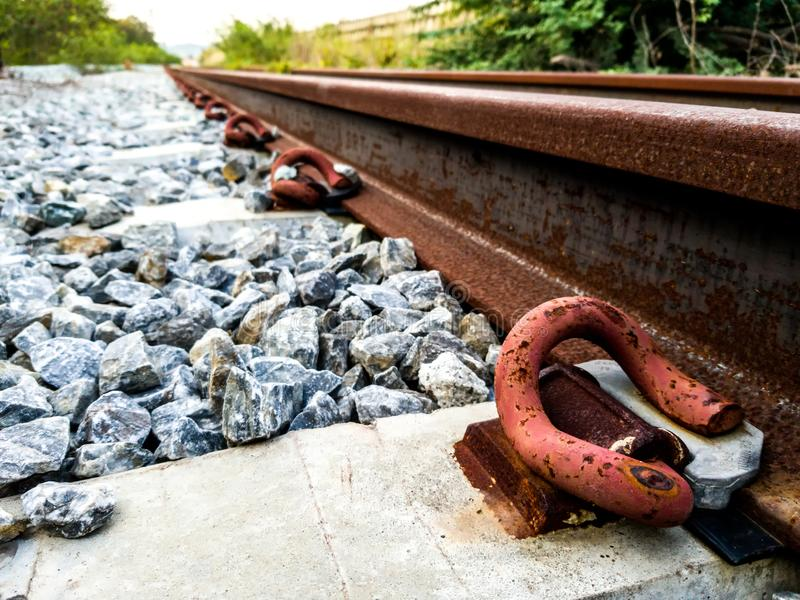 Rusty inactive railroad with concrete sleepers and rocks foundation. Red rusty inactive railroad with concrete sleepers and rocks foundation royalty free stock photography