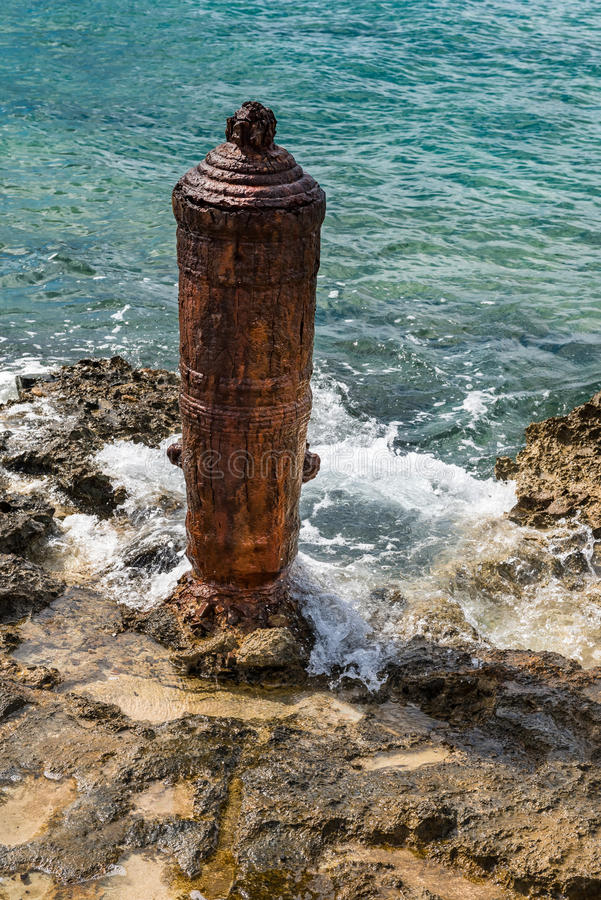 Red Rusty Steel Bollard on the Shoreline of the Caribbean sea an. Chored in the stone shoreline royalty free stock photo