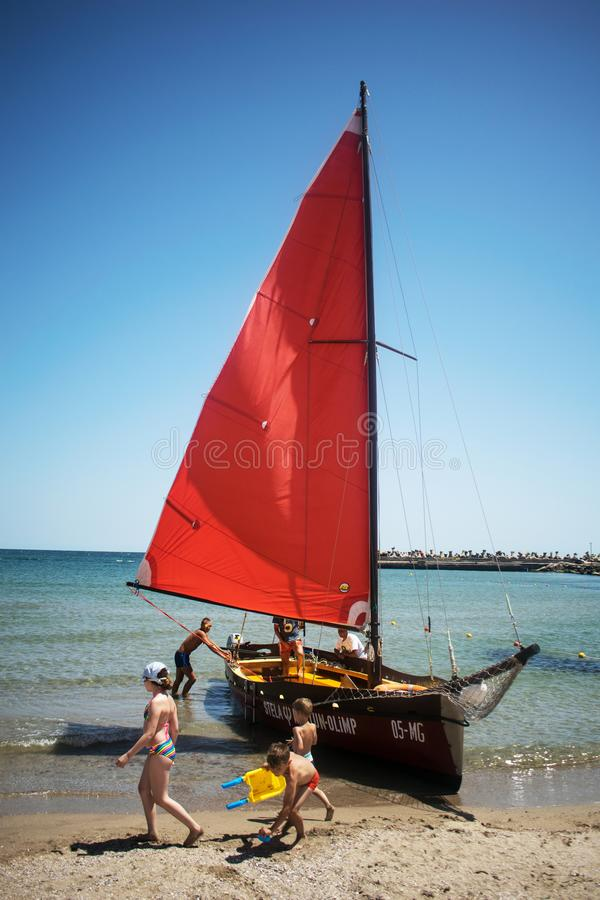 Location: Europe, Romania, Jupiter resort. Date: July, 07, 2019.  The red sailboat on the seashore is waiting to transport tourist royalty free stock photo