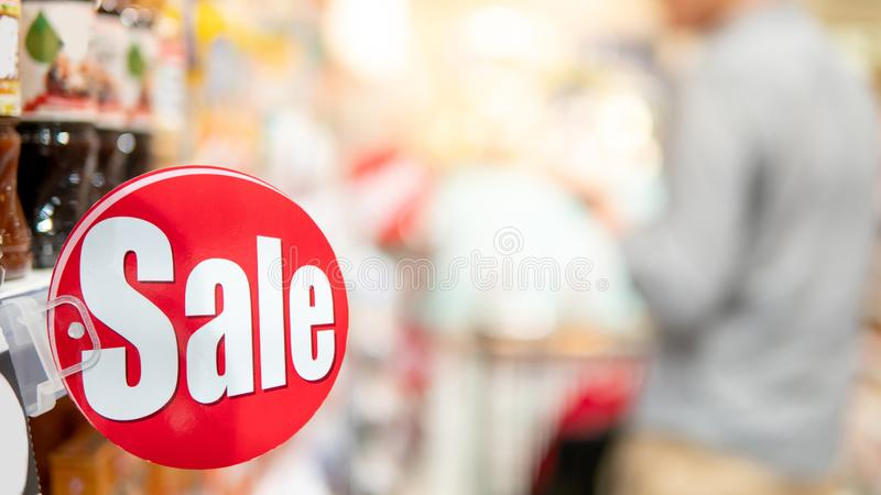 Red sale label on shelf in supermarket. Red sale label on product shelf in supermarket with blurred male shopper choosing food package in the background stock image
