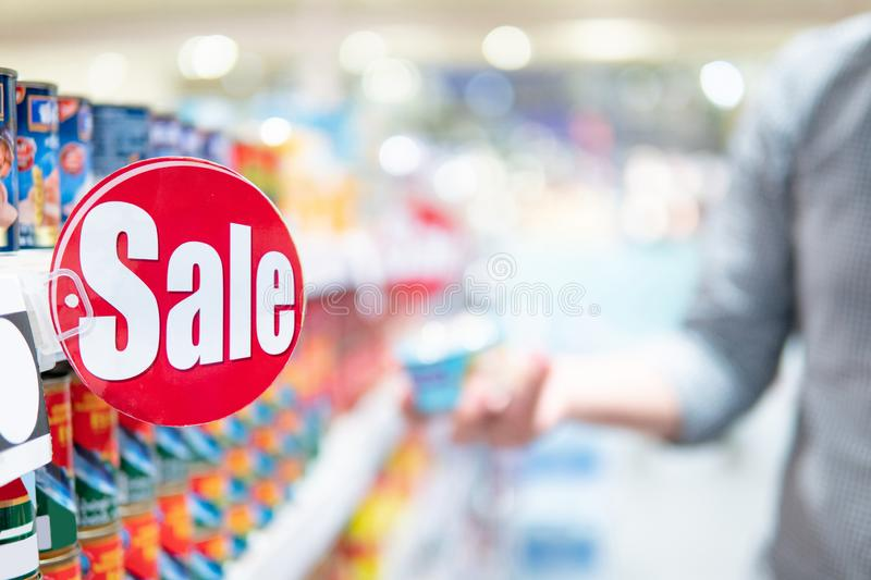 Red sale label on shelf in supermarket. Red sale label on product shelf in supermarket with blurred male shopper choosing food package in the background royalty free stock images