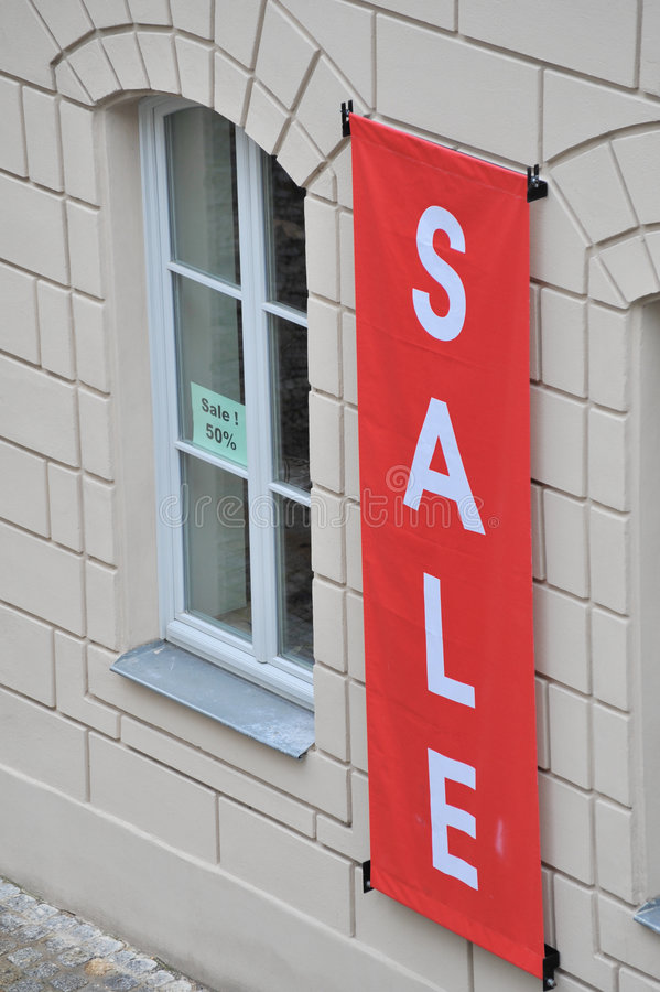 Red sale sign outside window. A red sale sign hanging outside a window of a store stock image