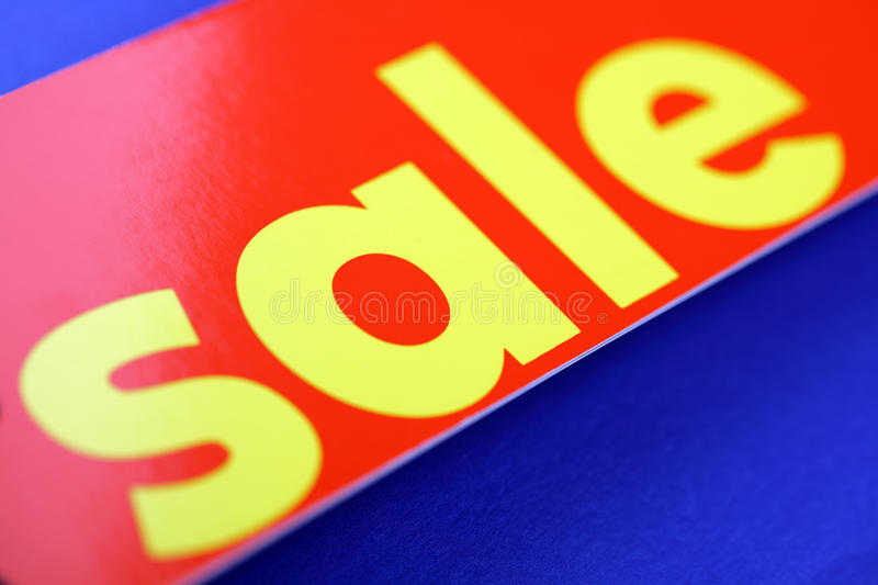 Red sale tag. Against a blue background with copyspace royalty free stock photo