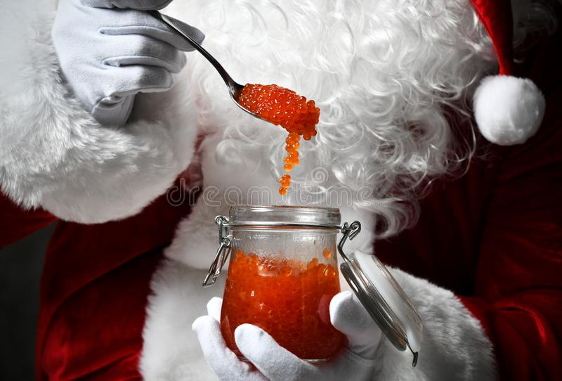 Closeup of a spoon full of red caviar falling back in a jar in Santa Claus hands in white gloves. New Year and Christmas stock images