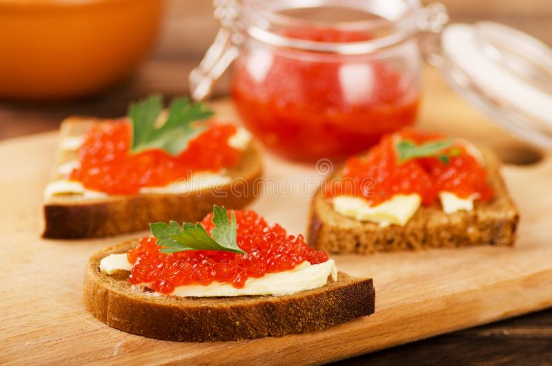 Red salmon caviar in sandwich and bowls stock photography