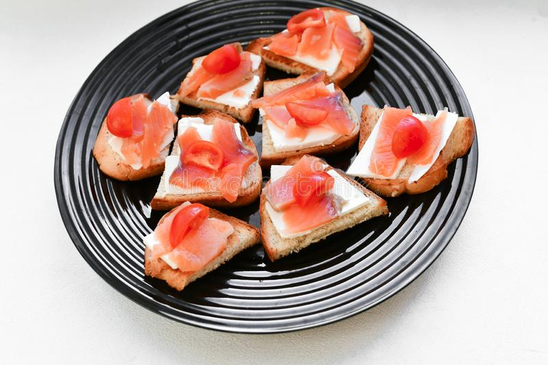 Red salmon on white bread. bagel and lox. view from above. black plate on a white background royalty free stock image