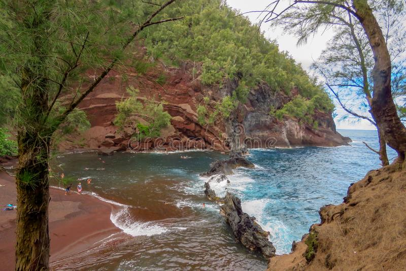 Red sand beach along the Road to Hana, Maui, Hawaii. Red sand beach or Kaihalulu Beach is a hidden cove with waves of the pacific ocean breaking on the rocks stock photography