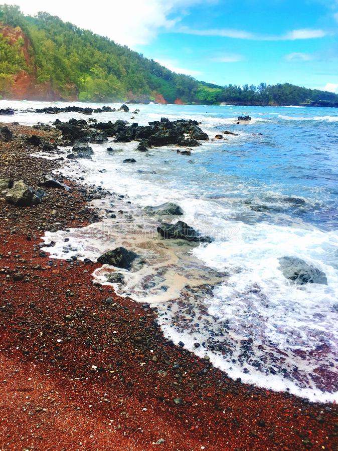 Red sand beach with lava rocks on the coast in Maui Hawaii stock images