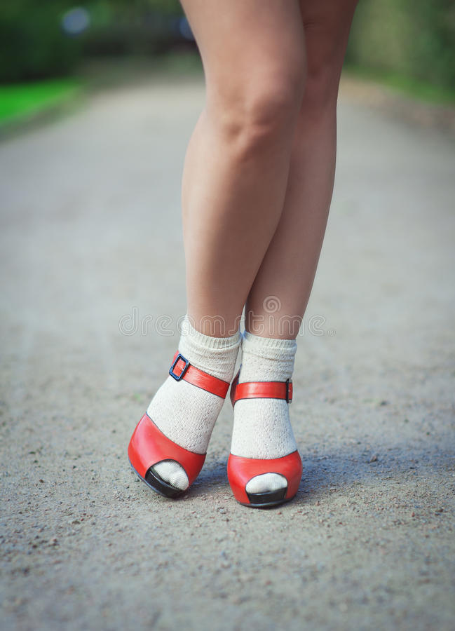 Red sandals with white socks on girl legs in fifties style. Outdoor royalty free stock image
