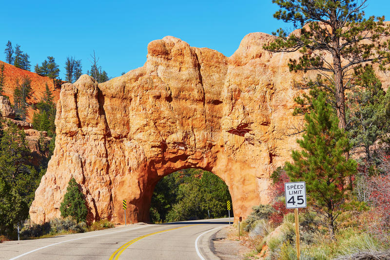 Red sandstone natural bridge in Bryce Canyon National Park in Utah, USA. Scenic view of stunning red sandstone natural bridge and asphalt road in Bryce Canyon royalty free stock images
