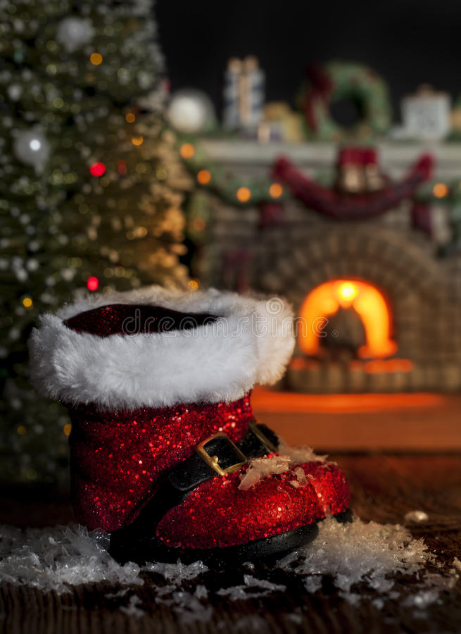 Red Santa Boots Melting Snow. Red Christmas Santa boots that have tracked in snow that is now melting from warmth of fireplace. Christmas tree and fireplace stock images
