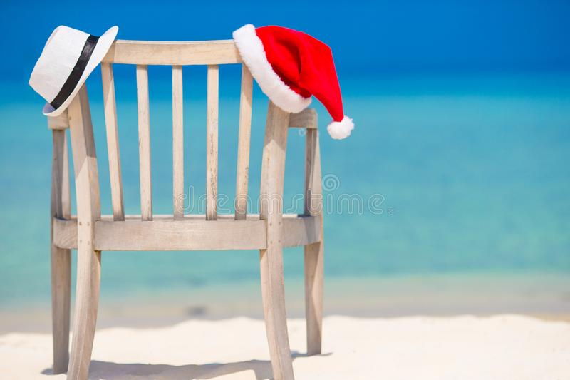 Red santa hat and white straw hat on beach chair at tropical vacation. Red santa hat on chair longue at tropical caribbean beach royalty free stock images