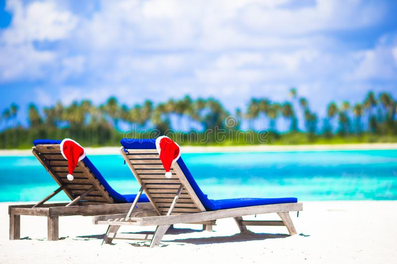 Red Santa Hat on chair at tropical white beach. Red santa hats on chair longue at tropical caribbean beach royalty free stock photography
