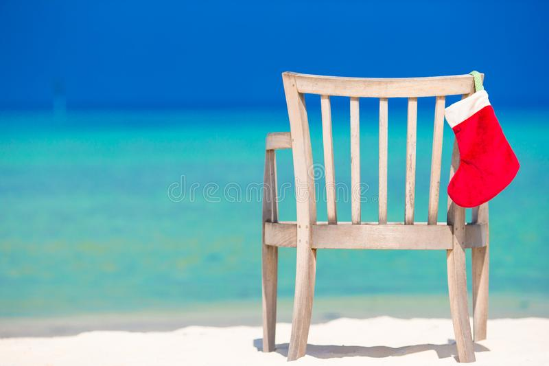 Red santa hat on chair at tropical white beach. Red santa hat on chair longue at tropical caribbean beach royalty free stock photography